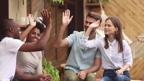 Lyckliga olika vänstudenter som ger fira mång--person som tillhör en etnisk minoritet höga fem kamratskap arkivfilmer