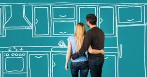 Lyckliga omfamna par som planerar deras hem- möblera för kök som är beträffande Arkivbilder