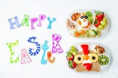 Lyckliga påskord med skolalunchaskar för ungar med mat in Royaltyfria Bilder