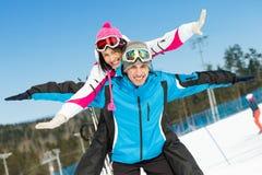 Lyckliga par av alpina skidåkare har gyckel royaltyfri bild