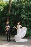 Lyckliga par av bruden och brudgummen som går i en parkera Lyckliga nygifta personer på bröllop i natur gör grön skogfotoståenden Royaltyfri Fotografi