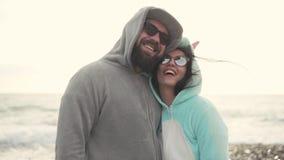 Lyckliga par av den iklädda sammetkigurumien för man och för kvinna på en solig kust arkivfilmer