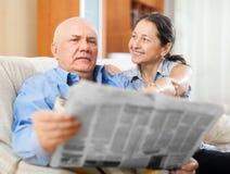 Lyckliga par av morföräldrar med tidningen Royaltyfri Fotografi