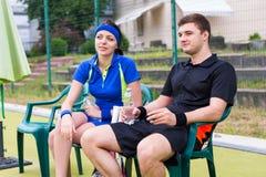 Lyckliga par av tennisspelare som har en vila och håller ögonen på gummina Royaltyfri Bild