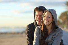 Lyckliga par av tonår som ser horisonten på solnedgången fotografering för bildbyråer
