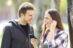 Lyckliga par av tonår som utomhus delar musik Royaltyfri Fotografi