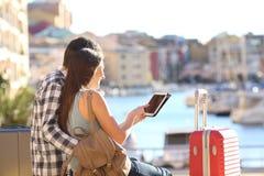 Lyckliga par av turister som använder en minnestavla på semester royaltyfria foton