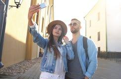 Lyckliga par av turister som tar selfie i gammal stad arkivfoton