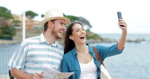Lyckliga par av turister som tar selfies på stranden på semester arkivfilmer