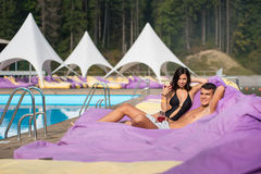 Lyckliga par - avslappnande near simbassäng för man och för kvinna på dämpade dagdrivare med drinkar på den lyxiga semesterorten Royaltyfria Foton