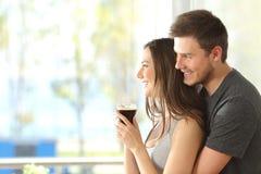 Lyckliga par eller förbindelse som ser till och med fönster arkivfoton