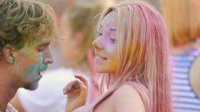 Lyckliga par färgade i pulverdansen som kysser och flörtar på den hinduiska festivalen