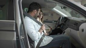 Lyckliga par fäster med bälten inom bilen arkivfilmer