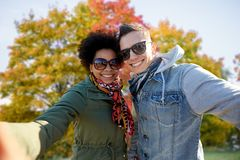 Lyckliga par för blandat lopp som tar selfie i höst arkivfoto