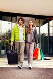 Lyckliga par går ut flygplatsen royaltyfri fotografi
