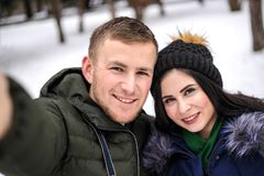 Lyckliga par gör selfie i vinter utomhus royaltyfri fotografi