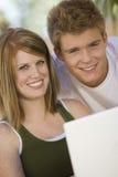Lyckliga par genom att använda bärbara datorn Royaltyfria Foton
