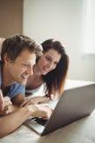 Lyckliga par genom att använda bärbara datorn på säng arkivfoton
