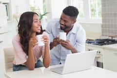 Lyckliga par genom att använda bärbara datorn tillsammans royaltyfria bilder