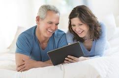 Lyckliga par genom att använda den Digital minnestavlan i säng Arkivfoto