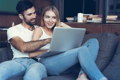 Lyckliga par genom att använda en bärbar dator på soffan arkivbild