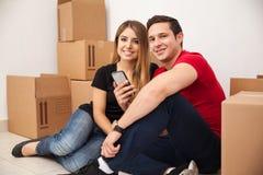 Lyckliga par genom att använda en smartphone Royaltyfri Foto