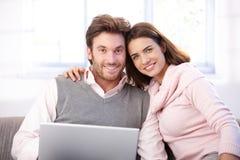 Lyckliga par genom att använda internet hemma Arkivfoto