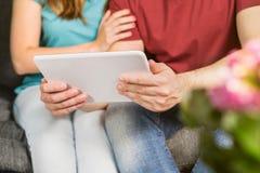 Lyckliga par genom att använda minnestavlan tillsammans på soffan arkivfoto