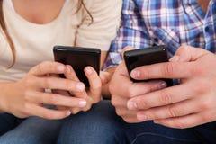 Lyckliga par genom att använda mobiltelefonen Royaltyfri Fotografi