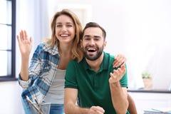 Lyckliga par genom att anv?nda video pratstund f?r konversation arkivbild