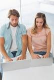 Lyckliga par genom att använda deras bärbara datorer Royaltyfri Foto