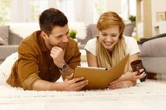 Lyckliga par genom att använda minnestavlan hemma Royaltyfria Bilder