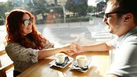 Lyckliga par har ett romantiskt datum i ett kaf? De rymmer sig h?nder f?r ` s Det ser s? gulligt arkivfilmer