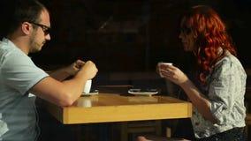 Lyckliga par har ett romantiskt datum i ett kaf? De rymmer sig h?nder f?r ` s Det ser s? gulligt stock video