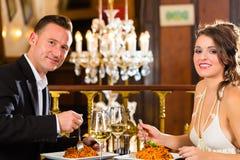 Lyckliga par har ett romantiskt datum i restaurang arkivbild