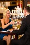 Lyckliga par har ett romantiskt datum i restaurang Royaltyfri Foto