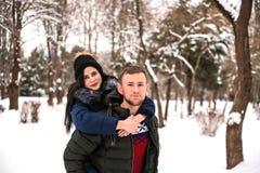 Lyckliga par har gyckel i vinter parkerar arkivfoton