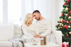 Lyckliga par hemma med julträdet royaltyfri foto