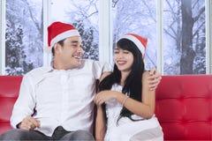Lyckliga par, i att skratta för julhatt Arkivfoton