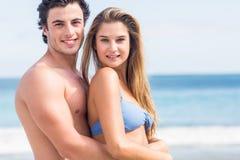 Lyckliga par i baddräkten som ser kameran och att omfamna Royaltyfri Bild