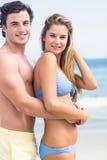 Lyckliga par i baddräkten som ser kameran och att omfamna Royaltyfri Fotografi