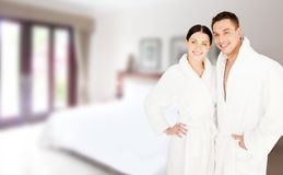 Lyckliga par i badrockar över brunnsorthotellrum Royaltyfri Foto
