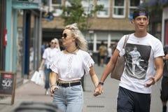 Lyckliga par i de vita T-tröja och att rymma händer som går på gatan Arkivbilder