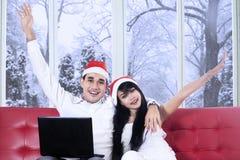 Lyckliga par i den santa hatten med bärbara datorn Royaltyfri Bild