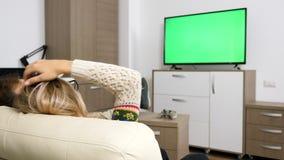 Lyckliga par i deras slags tvåsittssoffalägenhet som håller ögonen på en stor skärmTV med den gröna skärmen på den stock video