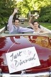 Lyckliga par i en konvertibel bil som vinkar med precis det frånskilda tecknet på det royaltyfri fotografi