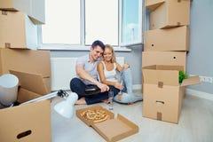 Lyckliga par i en ny lägenhet för en inflyttningsfest royaltyfri fotografi