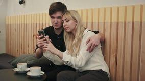 Lyckliga par i ett kaffehus som har frukosten och och anv?nder mobiltelefonen arkivfilmer