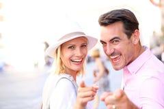 Lyckliga par i gatan som pekar kameran Royaltyfri Foto