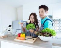 Lyckliga par i kök arkivfoto